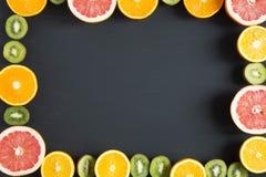 Mieszkanie nieatutowy Odgórny widok Pokrojone kolorowe świeże owoc: kiwi, pomarańcze, grapefruitowy, i mandarynka na czarnym tle obraz stock