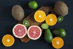 Mieszkanie nieatutowy Odgórny widok Pokrojone kolorowe świeże owoc: kiwi, pomarańcze, grapefruitowy, i mandarynka na drewnianej d fotografia stock