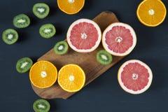 Mieszkanie nieatutowy Odgórny widok Pokrojone kolorowe świeże owoc: kiwi, pomarańcze, grapefruitowy, i mandarynka na drewnianej d obraz royalty free