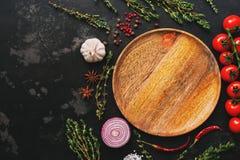 Mieszkanie nieatutowy pusty drewniany talerz, warzywa, pikantność i ziele na zmroku, drylujemy tło Pomidory, macierzanka, czosnek zdjęcia stock