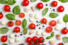 Mieszkanie nieatutowy skład z świeżymi pomidorami, mozzarella serowymi piłkami, czosnkiem i basilem na lekkim tle, Zdjęcia Royalty Free