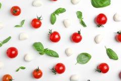 Mieszkanie nieatutowy skład z świeżymi pomidorami, mozzarella serowymi piłkami i basilem na lekkim tle, Zdjęcia Royalty Free