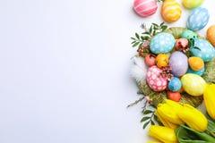 Mieszkanie nieatutowy skład z gniazdeczkiem, Wielkanocni jajka, upierza i kwitnie na koloru tle zdjęcia stock