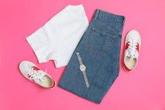 Mieszkanie nieatutowy skład z kobieta zegarem na różowym tle i ubraniami zdjęcie stock