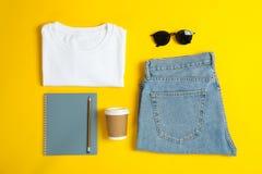 Mieszkanie nieatutowy skład z kobietami odzieżowymi i kreatywnie akcesoriami na żółtym tle zdjęcie stock