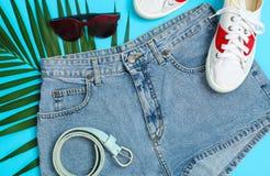 Mieszkanie nieatutowy skład z: kobiety odzieżowe i akcesoria, palmowy liść na błękitnym tle Lata t?o zdjęcie royalty free