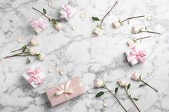 Mieszkanie nieatutowy skład z pięknymi różami i prezentów pudełkami na marmurowym tle obraz stock