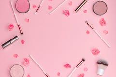 Mieszkanie nieatutowy sk?ad z dekoracyjnymi makeup produktami, menchiami i kwitnie na pastelowych menchii tle obrazy royalty free