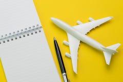 Mieszkanie nieatutowy zabawkarski samolot z piórem i biały czyści papierowego notepad fotografia stock