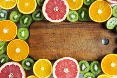 Mieszkanie Odgórnego widoku nieatutowa drewniana deska z pokrojonym kiwi, pomarańcze, grapefruitowym, i mandarynka na lekkim tle obraz royalty free