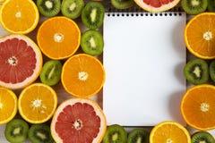 Mieszkanie Odgórnego widoku nieatutowy notatnik z pokrojonym kiwi, pomarańcze, grapefruitowym, i mandarynka na lekkim drewnianym  zdjęcia stock