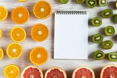 Mieszkanie Odgórnego widoku nieatutowy notatnik z pokrojonym kiwi, pomarańcze, grapefruitowym, i mandarynka na lekkim tle obraz royalty free
