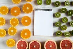 Mieszkanie Odgórnego widoku nieatutowy notatnik z pokrojonym kiwi, pomarańcze, grapefruitowym, i mandarynka na lekkim tle zdjęcie royalty free