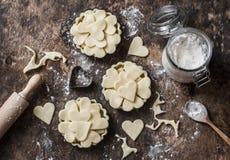 Mieszkanie walentynki ` s nieatutowego dnia wypiekowy tło Surowi jabłczani tartlets w wypiekowym naczyniu i wypiekowi składniki n Obraz Royalty Free
