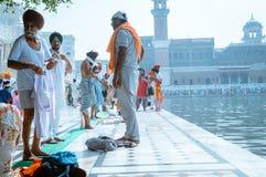 Mieszkaniec Pendżabu dewotki odmieniania traditionla Sikhijska pielgrzymia suknia przed świętym skąpaniem w stawie w frontowej Zł zdjęcie stock