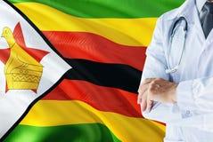 Mieszkaniec Zimbabwe Doktorska pozycja z stetoskopem na Zimbabwe flagi tle Krajowy system opieki zdrowotnej poj?cie, medyczny tem fotografia royalty free