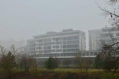 Mieszkaniowy budynek mieszkaniowy na tle jesień krajobraz w gęstej mgle w mieście zdjęcia stock