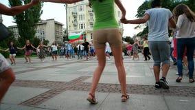 Mieszkanowie łączą ręki i tana w centrum miasta, ludowi tanowie, jedność naród, bulgarian flaga państowowa zbiory