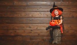 Śmieszna dziecko dziewczyna w czarownica kostiumu dla Halloween z dyniowym Ja Zdjęcie Royalty Free