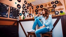 Śmieszna elegancka dziewczyna pije koktajl przez stra w barze Zdjęcie Royalty Free