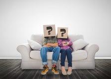 Śmieszna para jest ubranym pudełka z znakiem zapytania na ich głowie Fotografia Royalty Free