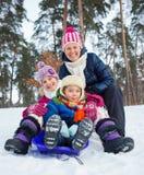 Śmieszna rodzina saneczkuje w krajobrazie Zdjęcie Royalty Free