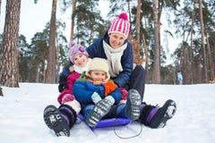 Śmieszna rodzina saneczkuje w krajobrazie Zdjęcia Royalty Free