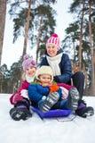 Śmieszna rodzina saneczkuje w krajobrazie Zdjęcia Stock
