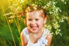 Śmieszna szczęśliwa dziecka dziecka dziewczyna śmia się w su w wianku na naturze Zdjęcie Royalty Free