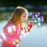 Śmieszna urocza mała dziewczynka dmucha mydlanych bąble Obrazy Royalty Free