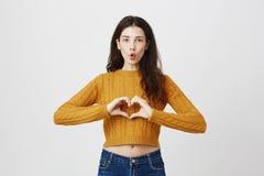 Śmieszne i seksowne caucasian kobieta modela falcowania wargi jak serce znak blisko klatki piersiowej, jest ubranym modnego cropp Zdjęcia Stock