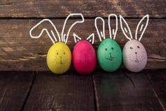 Śmieszni królika Easter jajka na nieociosanym drewnianym tle Obrazy Royalty Free