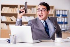 Śmieszny biznesmen z pistoletem w biurze Fotografia Royalty Free