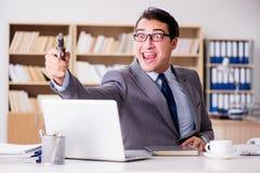 Śmieszny biznesmen z pistoletem w biurze Obrazy Stock