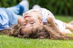 Śmieszny dziewczyny lying on the beach na trawie Fotografia Royalty Free