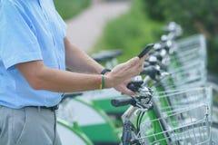 Mieten des Fahrrades vom städtischen Fahrrad, das Station teilt Stockbild