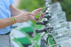Mieten des Fahrrades vom städtischen Fahrrad, das Station teilt lizenzfreie stockbilder