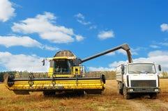 Mietitrebbiatrice che carica un camion nel campo Fotografia Stock Libera da Diritti