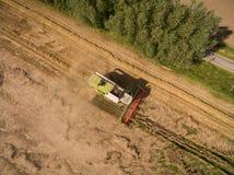 Mietitrebbiatrice - vista aerea della mietitrebbiatrice moderna a raccogliere il grano sul giacimento di grano dorato di estate Fotografie Stock