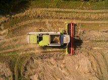 Mietitrebbiatrice - vista aerea della mietitrebbiatrice moderna a raccogliere il grano sul giacimento di grano dorato di estate Fotografie Stock Libere da Diritti