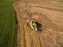 Mietitrebbiatrice - vista aerea della mietitrebbiatrice moderna a raccogliere il grano sul giacimento di grano dorato di estate Fotografia Stock
