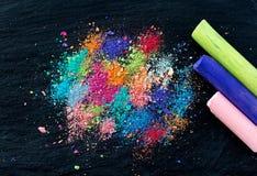 Miettes de craie multicolore sur un fond noir Joie, carnaval, panorama Un jeu pour des enfants Art image stock