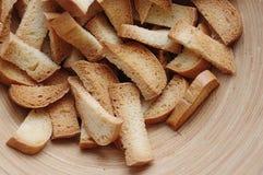 Miettes de pain macro dans la cuvette sur le fond bleu photos stock