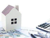 Mietvertragkontakt mit einem Architekturmodell und ein Taschenrechner und ein Stift und Schlüssel und USD-Dollar Lizenzfreies Stockfoto