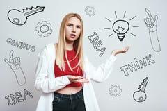 mig inte sure Bekymrad ung blond kvinna i tillfälligt visande lightbulb för bekläda, medan stå mot grå bakgrund arkivfoton