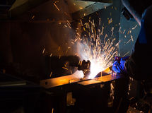 MIG welder uses torch to make sparks during manufacture. Of metal equipment Stock Photo