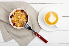 Migaja con las zarzamoras, cacahuetes y sésamo y taza de café imagen de archivo