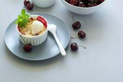 Migaja de la cereza con la harina de avena y el helado en cuenco en el escritorio de madera gris Comida sana del verano Imágenes de archivo libres de regalías