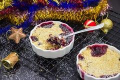 Migaja deliciosa hecha en casa dos con las bayas en ramekin repartido imágenes de archivo libres de regalías