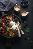 Migaja sana del granola de la avena del desayuno con las bayas, las semillas y el helado frescos en cacerola de la sartén del hie imagen de archivo libre de regalías